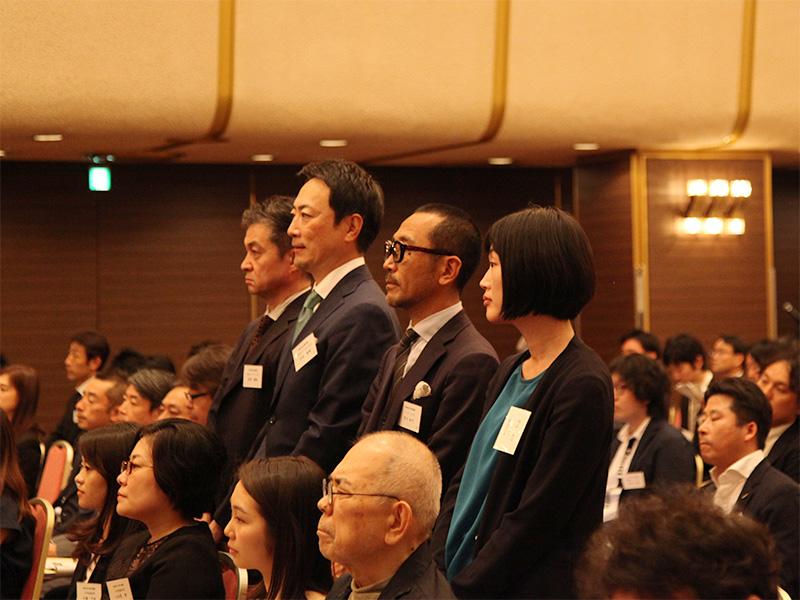 ▲受賞式で名前を呼ばれ立ち上がる吉田テクノワークス様とパラドックスのメンバー。