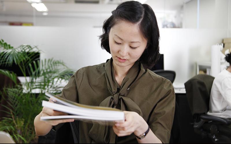 ▲「Small Company Branding‥‥」表紙の下の方にある、英語表記のタイトルを読む佐原。そうです、彼女は、アメリカ在住歴10年以上の帰国子女なのです(シカゴ大学という、名前からしてきっとすごい大学を卒業しています)。