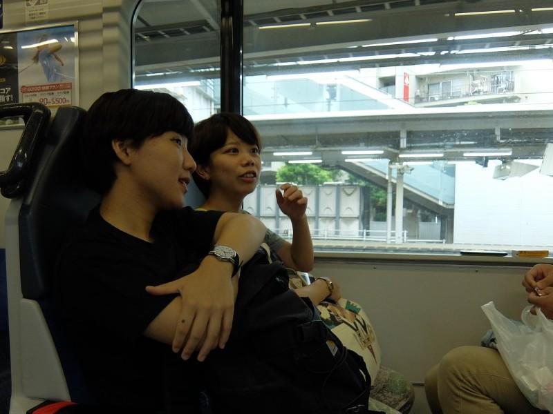 ▲電車の中、鎌倉で何をしようか話し合う広報メンバーたち。